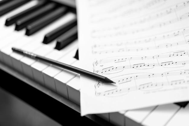 Mão com caneta e partitura - fundo musical