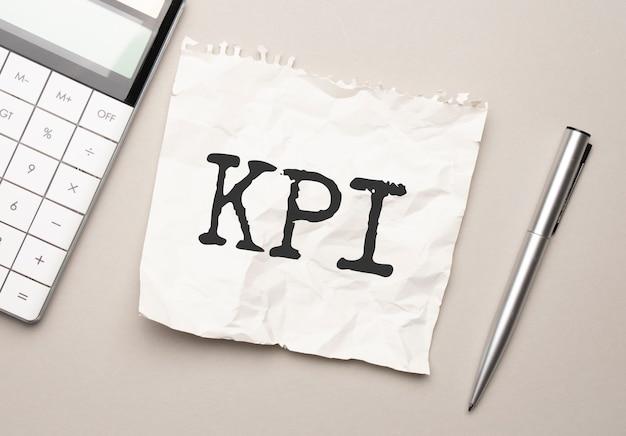 Mão com caneta vermelha. . bastão. calculadora e fundo branco. sinal de kpi no bloco de notas