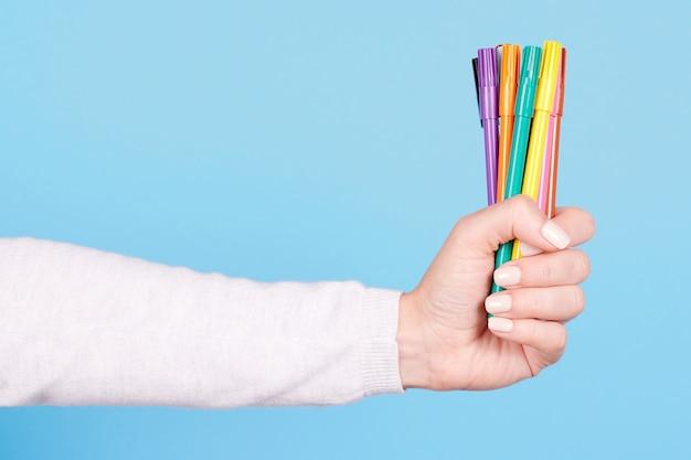 Mão com canetas de feltro coloridas isoladas