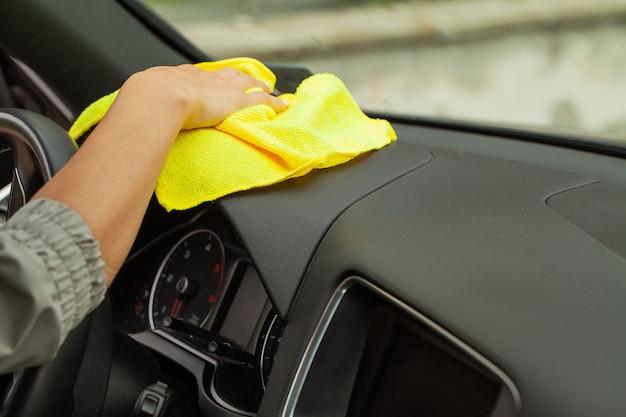 Mão com carro de polimento de pano de microfibra amarelo