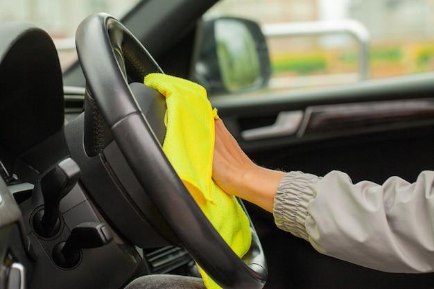 Mão com carro de polimento de pano de microfibra amarelo.