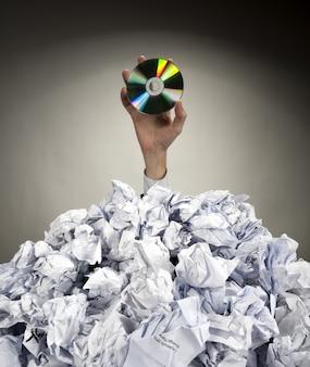 Mão com cd se estende de uma pilha de papéis