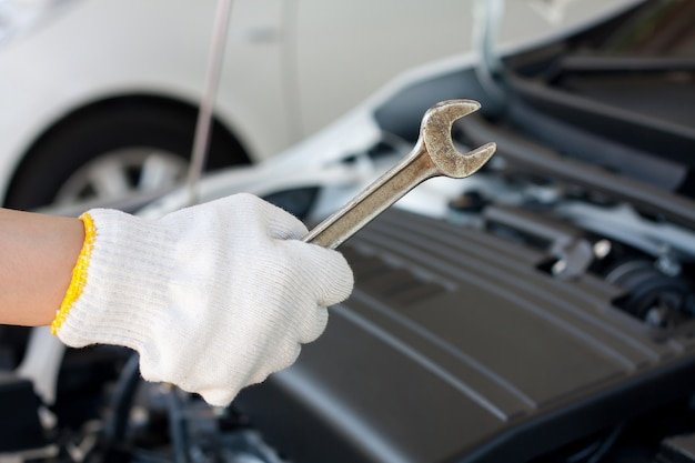 Mão com chave para consertar e verificar o motor do carro