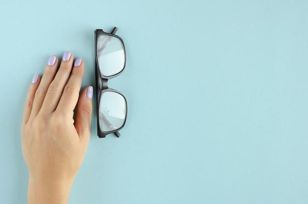 Mão com composição de óculos sobre fundo azul.