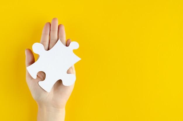 Mão com composição de quebra-cabeças em fundo amarelo.