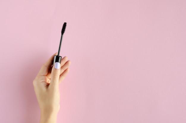 Mão com composição de rímel preto sobre fundo rosa.