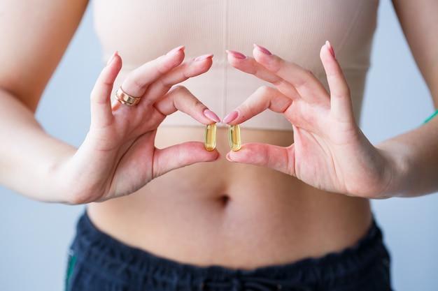 Mão com comprimidos. a mulher está tomando medicamentos para melhorar a imunidade. norma diária de vitaminas, preparações eficazes, farmácia moderna para a saúde.