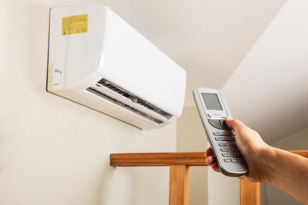 Mão com controle remoto direcionado ao condicionador na parede