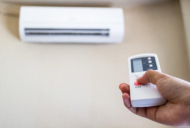 Mão com controle remoto direcionado ao condicionador