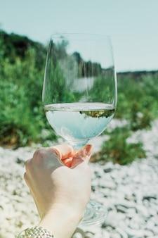 Mão com copo de vinho branco no fundo verde da natureza do verão