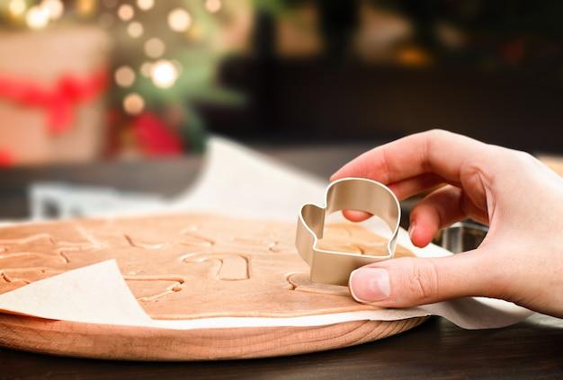 Mão com cortador de biscoitos faz pão de gengibre de natal