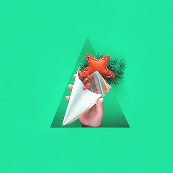 Mão com decorações naturais, caixa de presente em papel ofício e estrela vermelha artesanal de feltro macio em cone de madeira compensada no orifício de papel triangular. feliz zero desperdício férias de inverno