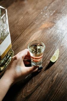 Mão com doses de tequila na mesa de madeira