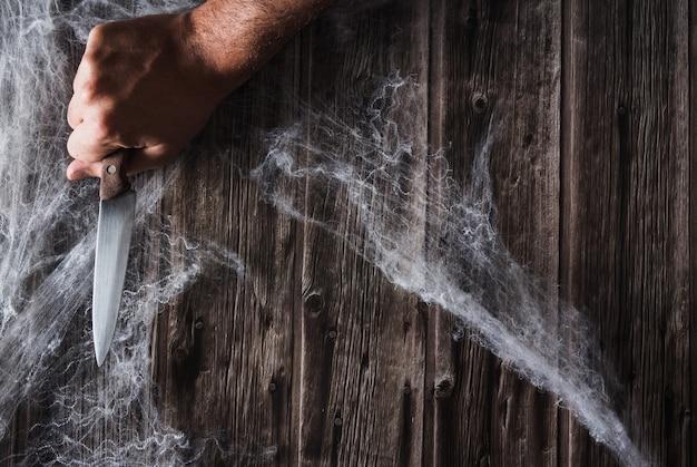 Mão com faca em teias de aranha. banner de halloween. copie o espaço. foco seletivo.