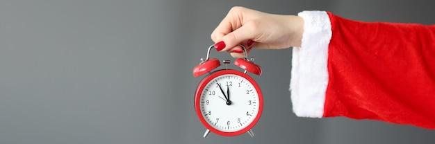 Mão com fantasia de papai noel tem despertador vermelho. conceito de celebração de ano novo e natal