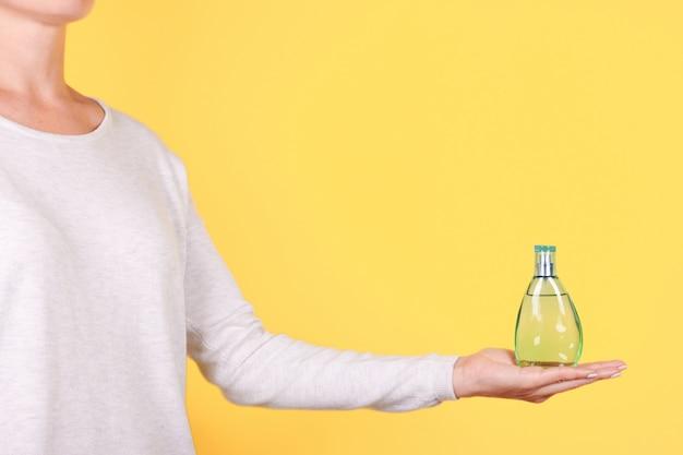 Mão com frasco de perfume de luxo isolado