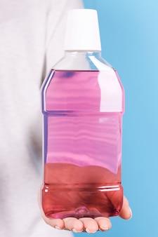 Mão com frasco roxo de enxaguante bucal isolado