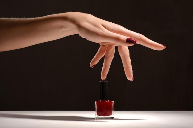 Mão com garrafa vermelha de manicure e esmalte