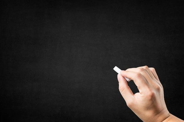 Mão com giz em um quadro-negro