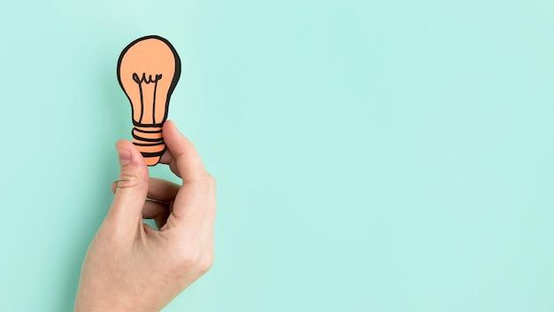 Mão com lâmpada de papel
