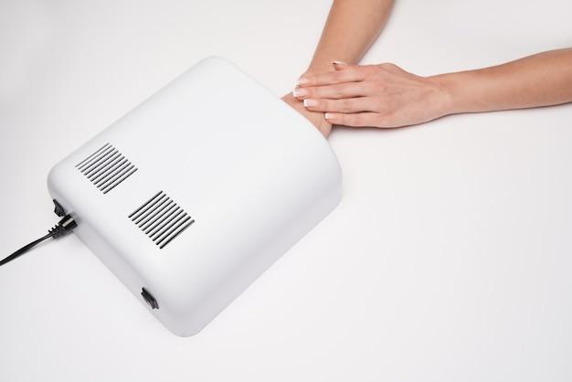 Mão com lâmpada ultravioleta para unhas sobre superfície clara