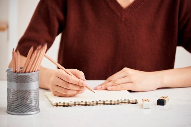 Mão com lápis de cor e folha de papel em branco na mesa branca Foto Premium