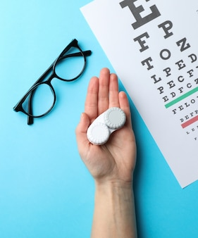 Mão com lentes de contato, óculos e gráfico de teste de olho na superfície azul, vista superior