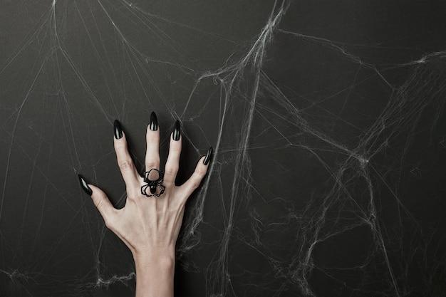 Mão com longas unhas pretas e anel de aranha em um fundo preto com teias de aranha. conceito de feriado feliz dia das bruxas