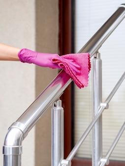 Mão com luva cirúrgica, limpeza do trilho de mão com pano