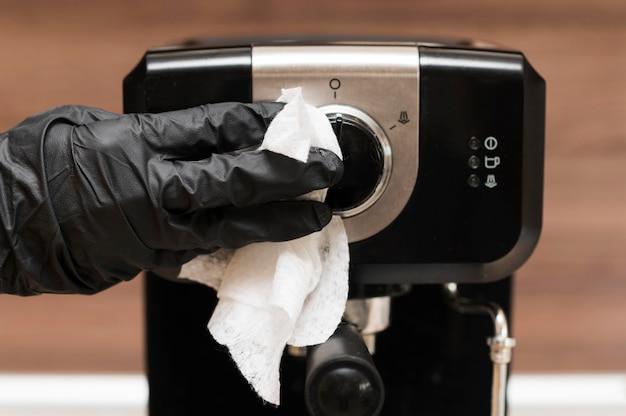 Mão com luva cirúrgica para desinfetar a máquina de café expresso