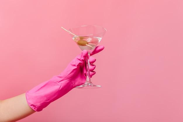 Mão com luva de borracha segurando copo de martini na parede rosa