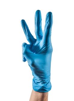 Mão com luva de látex azul mostrando três dedos