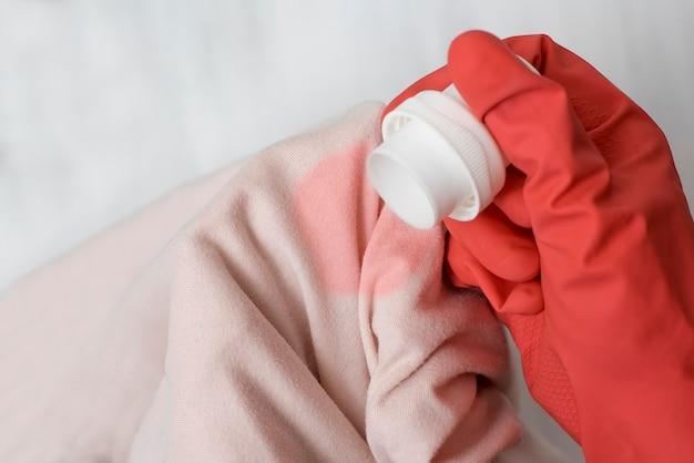 Mão com luva, derramando o líquido sobre a mancha nas roupas. fechar-se