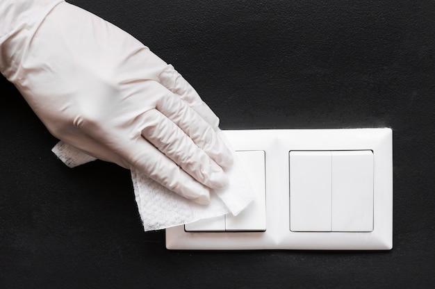 Mão com luva desinfetando interruptores de luz