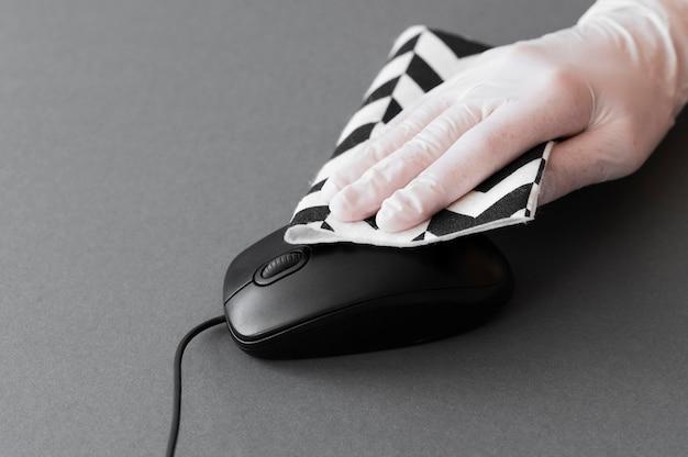 Mão com luva para desinfecção do mouse
