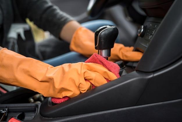 Mão com luva usando pano úmido e spray antibacteriano para limpeza do interior do carro