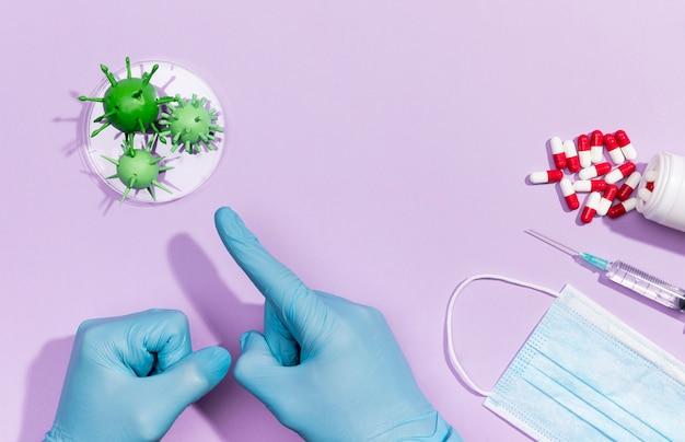 Mão com luvas apontando para bactérias