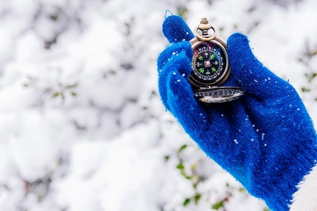 Mão com luvas de lã segurando uma bússola na neve