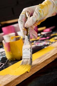 Mão com luvas de pintura com pincel