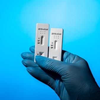 Mão com luvas de proteção segurando testes ambiciosos