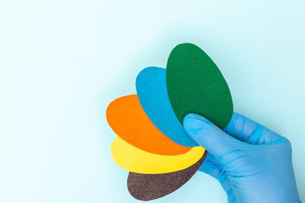 Mão com luvas médicas protetoras segurando ovos de papel de páscoa multicoloridos em um fundo azul