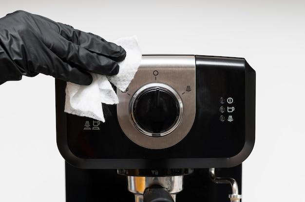 Mão com luvas para desinfetar a máquina de café expresso