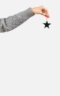 Mão com manicure segurando enfeites de estrela em fundo cinza com espaço de cópia