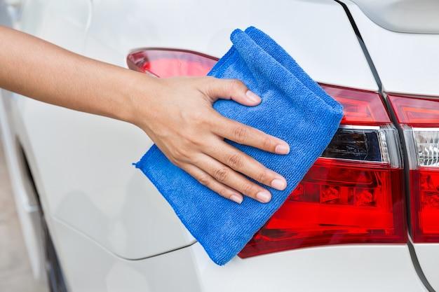 Mão com o carro azul do branco da lanterna traseira da limpeza de pano do microfiber.