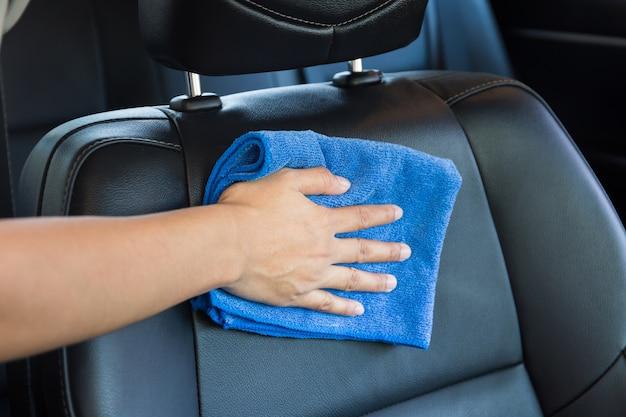 Mão com o pano moderno do microfiber que limpa o carro moderno interior.