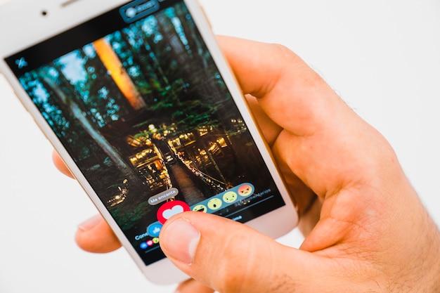 Mão com o telefone e o aplicativo do facebook