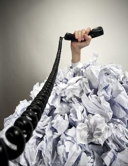 Mão com o telefone se estende de uma pilha de papéis