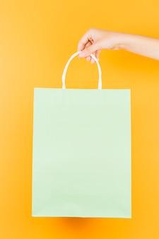 Mão com pacote de compras de salada