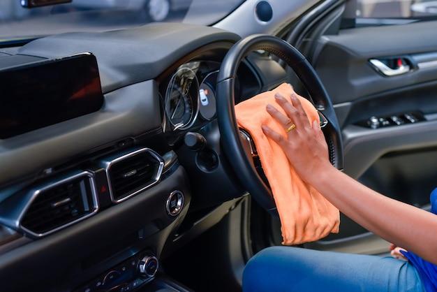 Mão com pano de microfibra limpeza interior do carro.