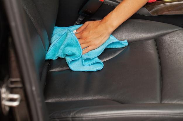 Mão com pano de microfibra para limpar interior do carro moderno.